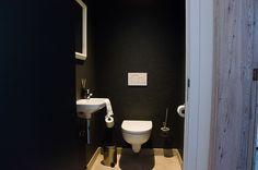 donkergrijze muren en deur met wit en inox sanitair