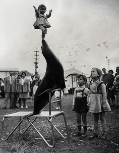 A seal puts on a show by balancing a doll before young viewers at a performance of the Krone Circus in Aachen, Germany, 1961.