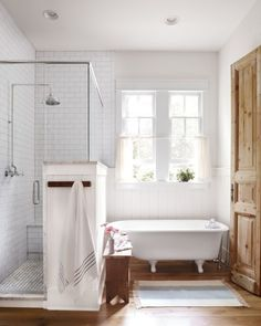 Beautiful modern farmhouse style bathroom with vintage clawfoot tub, knotty pine door and inspiration on Hello Lovely Studio Tap the link now to see where the world's leading interior designers purchase their beautifully crafted, hand picked kitchen, bath and bar and prep faucets to outfit their unique designs.