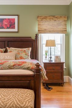Soft green walls complement the warm wood furnishings in this comfy and inviting master bedroom. Floral bed linens and artwork add color and life to the space.
