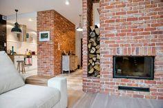 Czerwone cegły łączą aranżację salonu z aranżacją kuchni, zapewniając spójność w części dziennej domu w skandynawskim...