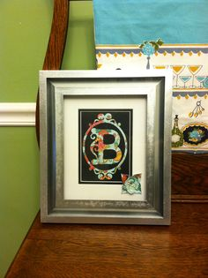 Michael's picture frame spray painted silver & Cricut cut monogram and flower.