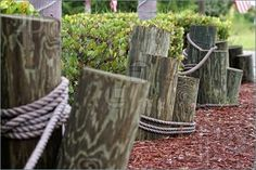 Pics of wooden poles are mounted in the ground and tied together with rope making for a nautical type fencing or boundary on an overcast day