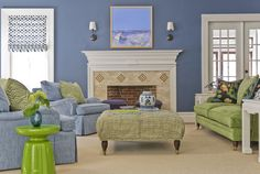 Clean design and plush seating will make you want to curl up with a good book in this cozy living room. The periwinkle walls match the upholstered armchairs, and the green accents complement the space, preventing it from looking too monochromatic.