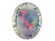 An absolutely magnificent black opal and diamond cluster ring mounted in platinum. Art Deco ring circa 1925 set to centre with an opal weighing approximately 13.00 carats, in a six double claw setting. Set to either shoulder with a close set baguette cut diamond, remainder of diamond border is made up of twenty-six 'eight cut' stones in grain settings. The play of colour in this opal is outstanding.