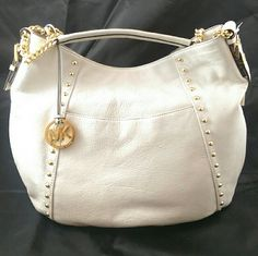 """Michael Kors Middleton Medium Shoulder Bag Vanilla This Michael Kors shoulder tote, NWT, is a perfect everyday bag. Not only is it a beautiful, neutral leather, but the size, 15"""" x 5"""", with a 14"""" height and 7"""" drop, will fit everything you need without dislocating your shoulder.  There's one long outside pocket on the front, four slides inside along with one long zippered pocket.  Two lines of gold tone studs add character. Magnetic closure. Includes a long MK fob. Michael Kors Bags Shoulder…"""
