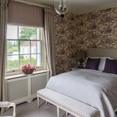 Pack a decorative punch with a feature wall papered in an eye-catching purple toile de Jouy design. Gingham fabric on an upholstered chair and bench have been combined with painted cream furniture for a classic look that's full of charm