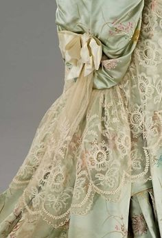 Back of elegant dress, pale green fabric with pink embroidered roses, partially covered with edru lace, ecru satin bow - oh, my!