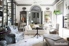 Painted floors, a slipcovered sofa, and pale blue fabrics give a light, airy feel.