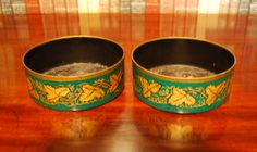 """A delightful pair of toleware decanter coasters decorated with gilt vines on a green background. These are 5.2"""" diameter each."""