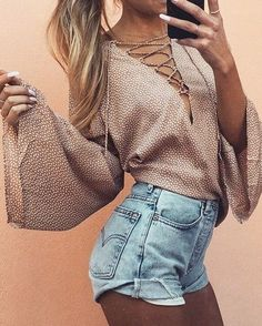 High waisted, cuffed denim shorts, lace up blouse with long, wide sleeves