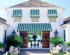 This has blue-white stripped awnings and the door, tropical plants on the outside, I see a beach in the background.