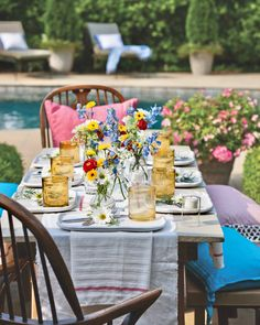 With balmy days here to stay, the time is right for poolside dining. Basic linens set a clean backdrop for assorted flowers casually arranged in miniature vases. #southernladymag #tablescape #tablescapes #alfresco #diningalfresco #tabletopinspo #styling #tablestyling