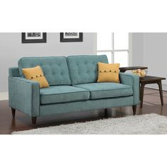 Add style to the home with this mid-century inspired design composed from a durable construction of metal with medium walnut finish wood. The retro shape and soft aqua colored fabric create an updated vintage feel.
