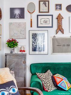A decoração do apartamento da ilustradora e designer Ana Strumpf passeia por diferentes estilos e épocas com naturalidade. Na sala de estar, os quadros e objetos de decoração na parede dão charme extra ao ambiente.