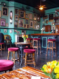 Eclectic feel by a colorful coffee shop. burgundy velvet chairs and teal wall color