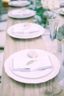 Wooden trestle tables with cream charger plates and grey linen napkins