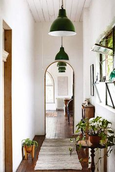 Organic-infused entryway with a natural rug runner, tons of potted indoor plants, antique side table and console, and glossy green lacquered pendant lights.