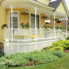 Decorative spindles, combined with flowers in hanging baskets and rail boxes, dress up the rounded front porch of this Victorian-style home.