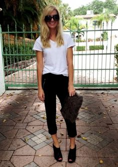 Cropped sweatpants look chic with a half-tucked tee, a clutch and booties.