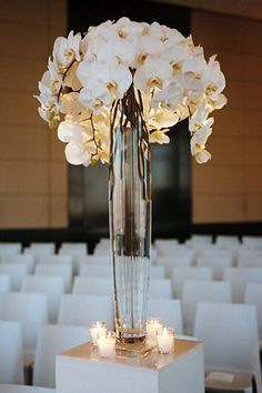 Ok this is what I want our to be, tall thin glass vase, beautiful big flowers at top with grenery and lighted branches!!! Modern, tall arrangements of phalaenopsis orchids