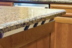 """Hiding electrical outlets on an island, low profile fits within 1.5"""" overhang:  Remodeler Rob Baugher used to use flat strips, but now prefers Task Lightingís angled strips. """"You can get the plug in without scraping your..."""