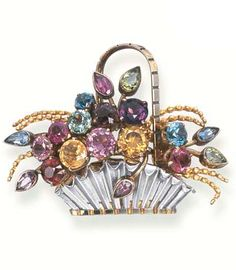A GEM-SET BROOCH The circular and pear-shaped gemstones including zircons, peridot, garnet, amethyst and aquamarine to the 9k yellow and white gold basket, 4.5 cm. wide