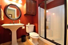 This full bath is lovely with ceramic tile floor, pedestal sink, designer wall color and a glass enclosed shower.