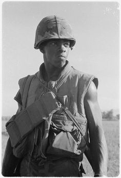 A Marine of Company I 3rd Battalion 1st Marine Regiment cross an open field while on patrol 8 miles south of the city of Da Nang Vietnam 1969.