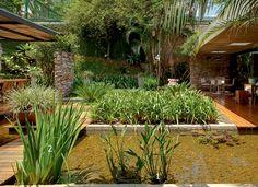 Em uma moderna construção da década de 1970, o jardim desbanca a sala de estar. Espécies tropicais, área gourmet e uma feliz combinação de elementos não deixam dúvida: é lá que tudo acontece