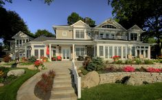 The vision for this over 7,000 sq. ft. custom lake home came from the homeowner's many years of traveling to coastal areas out east and in Michigan. One of the most unique features (and the owner's favorite room) of the home is the geometric, octagonal screened-in sun porch with French doors. Custom built home, lake home, luxury home, cedar shingles, retaining walls, Michiana, hardscaping, landscaping