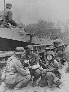 """1941, Ukraine, Kiev, Des soldats allemands dont un """"Gefreiter"""" blessé s'abritent derrière semi-blindé Sd.Kfz 250 lors des combats"""