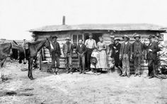 A pioneer family, along with friends, posed for a portrait in front of their hand-built home in Wyoming in 1870. Credit - The New York Times