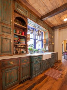 Distressed kitchen cabinets, reclaimed hardwood flooring and ceiling paneling with exposed beams.