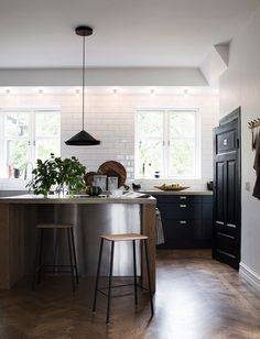 Black cabinets, stainless steel + wood island, concrete countertops, rustic wood…
