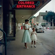 "Joanne Wilson and her niece stood in front of a movie theater in downtown Mobile, Alabama in 1956, dressed in their Sunday best, but the neon sign that loomed overhead — ""Colored Entrance"" — cast a despairing shadow. (Photo: Gordon Parks)"