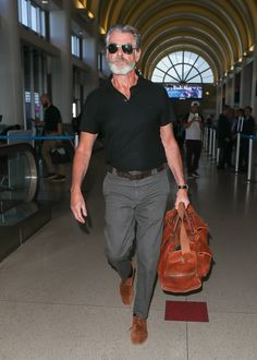 Pierce Brosnan nails airport style time and time again Pierce Brosnan, Italy Fashion, Mens Fashion, Polo Shirt Outfits, Most Stylish Men, Black Polo Shirt, Grey Trousers, Glamour, Travel Shirts