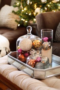 all the ornaments on the tree are white, clear or silver... with added pops of colored ornaments throughout the rest of the room... This way the color scheme was balanced.  Filling these cloches with ornaments instantly adds a touch of glamour.
