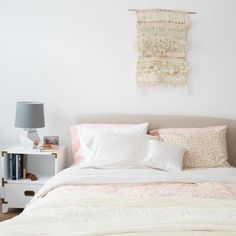 A muted & quiet master bedroom, featuring a large weaving, campaign nightstands, organic bedding and a velvet quilt
