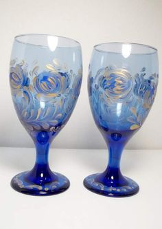 """Set of two blue glass vintage glassware hand painted in the style of rosemaling, folk art. They were hand painted using blue and metallic gold acrylic glass enamel paint. Non-toxic. Hand washing recommended. Artist signed. 7"""" H, 3"""" across top. Gold Wine Glasses, Vintage Wine Glasses, Vintage Glassware, Metallic Gold Paint, Flower Bottle, Scandinavian Folk Art, Enamel Paint, Porcelain Ceramics, Glass Art"""