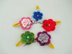 Olá pessoal! Mais um conjunto, em crochet, de ganchinhos, com flores e cores variadas. Para este conjunto usei ganchos ou ti-tacs amarelos, pois o cabelo da menina é louro. Fiz todos com o mesmo desenho da flor mas com várias cores e combinei as cores das pérolas com as cores do fio. Us