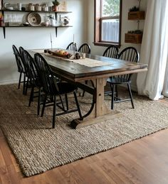 dining room 278589926937945254 - full room picture of dining room with jute rug underneath long wood table and 8 black wood chairs Source by keystoinspire Farmhouse Dining Room Rug, Dining Table Rug, Area Rug Dining Room, Timber Dining Table, Dining Room Design, Dining Room Furniture, Rugs In Living Room, Carpet In Dining Room, Black Dinning Table