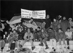 """New Year's Eve in Berlin (December 31, 1989)  During their first New Year's celebration together at Berlin's Brandenburg Gate, East and West Germans waved West German flags and expressed New Year's wishes on banners. The one featured here reads: """"Peace and all the best for a new Germany. East greets West."""""""