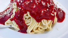 Spaghettieis is a German ice cream specialty that looks like a plate of spaghetti. In the dish, an often light or white colored ice cream is extruded through a modified Spätzle press or potato ricer, giving it the appearance of spaghetti. It is then placed over whipped cream and topped with strawberry sauce (to simulate tomato sauce) and either coconut flakes, grated almonds, or white chocolate shavings to represent the Parmesan cheese.