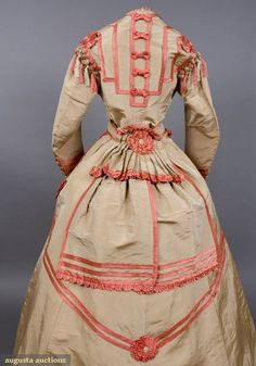 """Detail of a Silk Visiting Dress, 1860s """"Three-piece buff changeable ribbed taffeta, trimmed with bright coral satin bands, scallops, bows, rosettes and Van Dyke points: front buttoning boned bodice with high neckline; belt with attached back peplum; trained unlined skirt, gold stamped label """"Louis Hille Tailleur Pour Dames 398 Rue St Honore Paris""""[…] Featured in April 1998 ANTIQUES Magazine"""" – Augusta Auctions"""