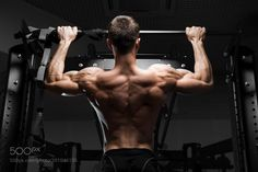 Athlete muscular fitness male model pulling up on horizontal bar by krisanow2007