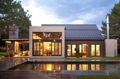 A Captivating Facade House With Grey Exposed Brick Wall And Wooden Matreial Combination Plus Warm Lighting With Terrific Swimming Pool Refined and rustic elements create a complex atmosphere at home