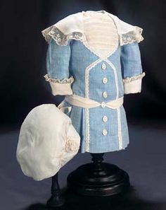 """Pretty Blue Cotton Dress and Cap 4"""" shoulder width. 10"""" overall length. To fit child doll about 15""""-16"""". Of patterned blue cotton,the dress has set-in yoke with tucking,pleats at the sides and back below the hips,coat- style sleeves with turn-up cuffs,and a wide collar with lace edging to matching the cuffs; with pearl buttons and cotton lace border,and with a matching cap. Circa 1918."""