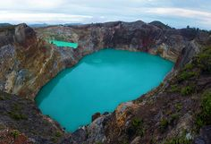 Mount Kelimutu has three coloured lakes, above is Tiwu Nuwa Muri Koo Fai (Lake of Young Men and Maidens) and Tiwu Ata Polo (Enchanted Lake) while Tiwu Ata Mbupu (Lake of Old People) is located in the westernmost of the others.  The first two lakes are typically green or red in color though they do vary on periodic basis.  Kelimutu National Park, Flores, East Nusa Tenggara, Indonesia.  (by Eye In The Sky Photography)