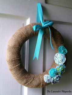 """14"""" Burlap wrapped wreath with turquoise rolled fabric flowers and a grosgrain bow for hanging."""